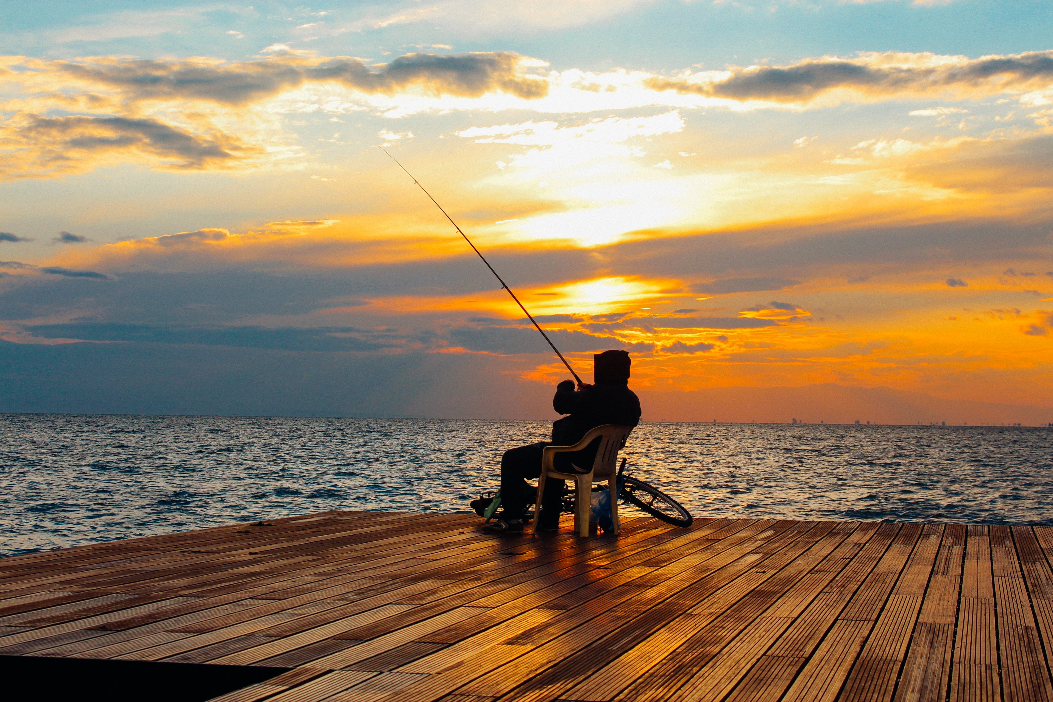 Silhouette of Person Sitting on Chair Holding Fishing Rod Near Body of Water during Golden Hour