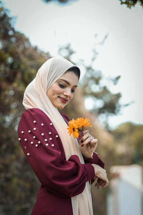 Shallow Focus Photo of Woman in Beige Hijab Headdress With Orange Flowers
