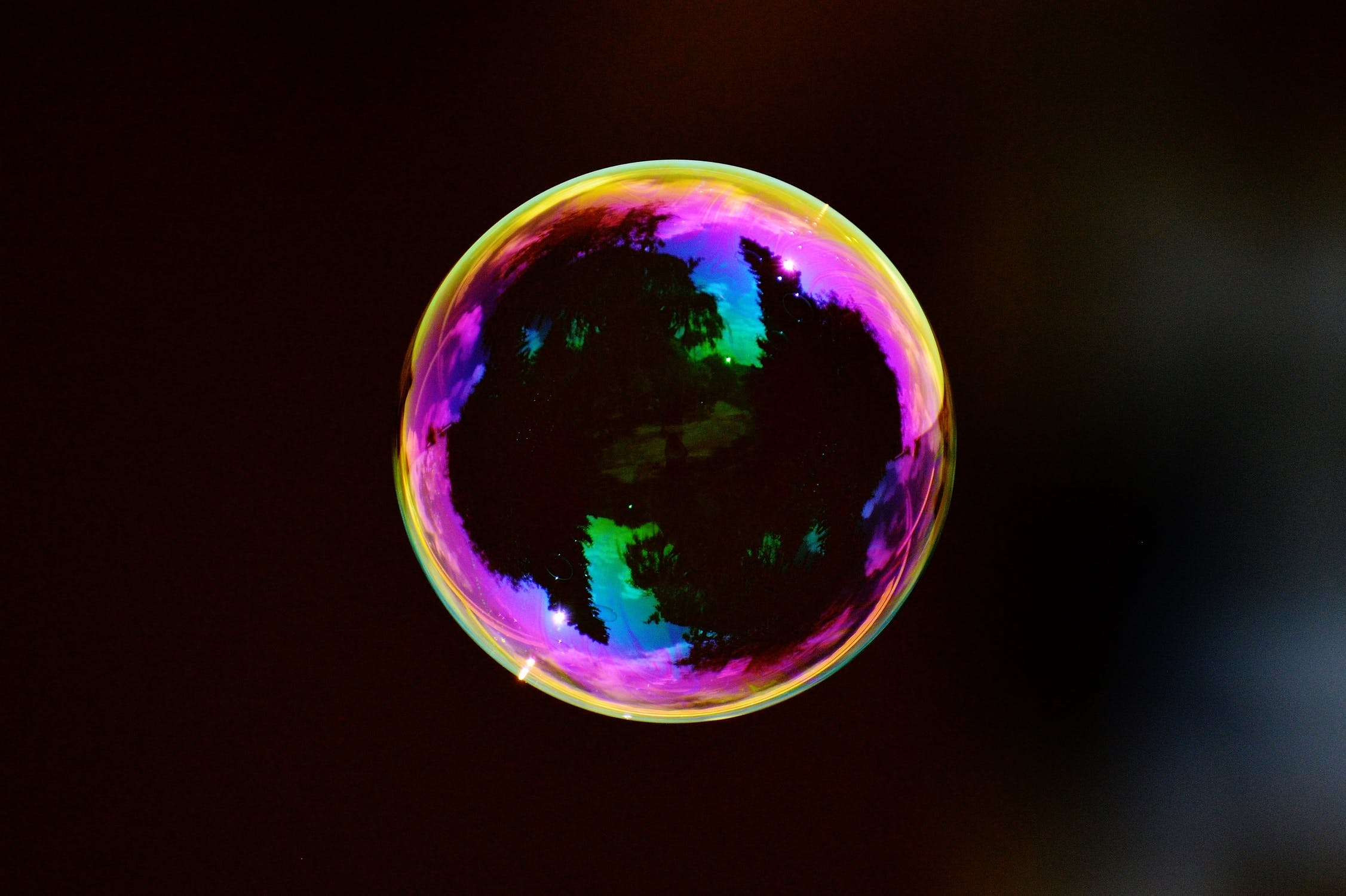 A soap bubble floating in front of a black background