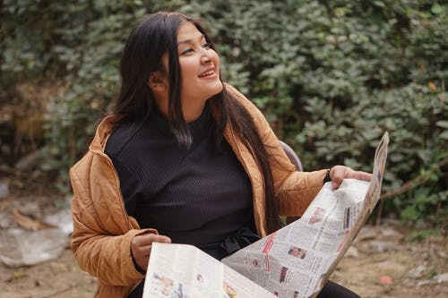 Asian Woman Holding a Newspaper