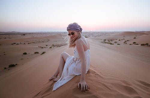 Woman Wearing White Dress Sitting on Sand