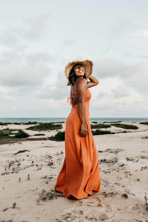 Woman Wearing Orange Dress and Sun Hat