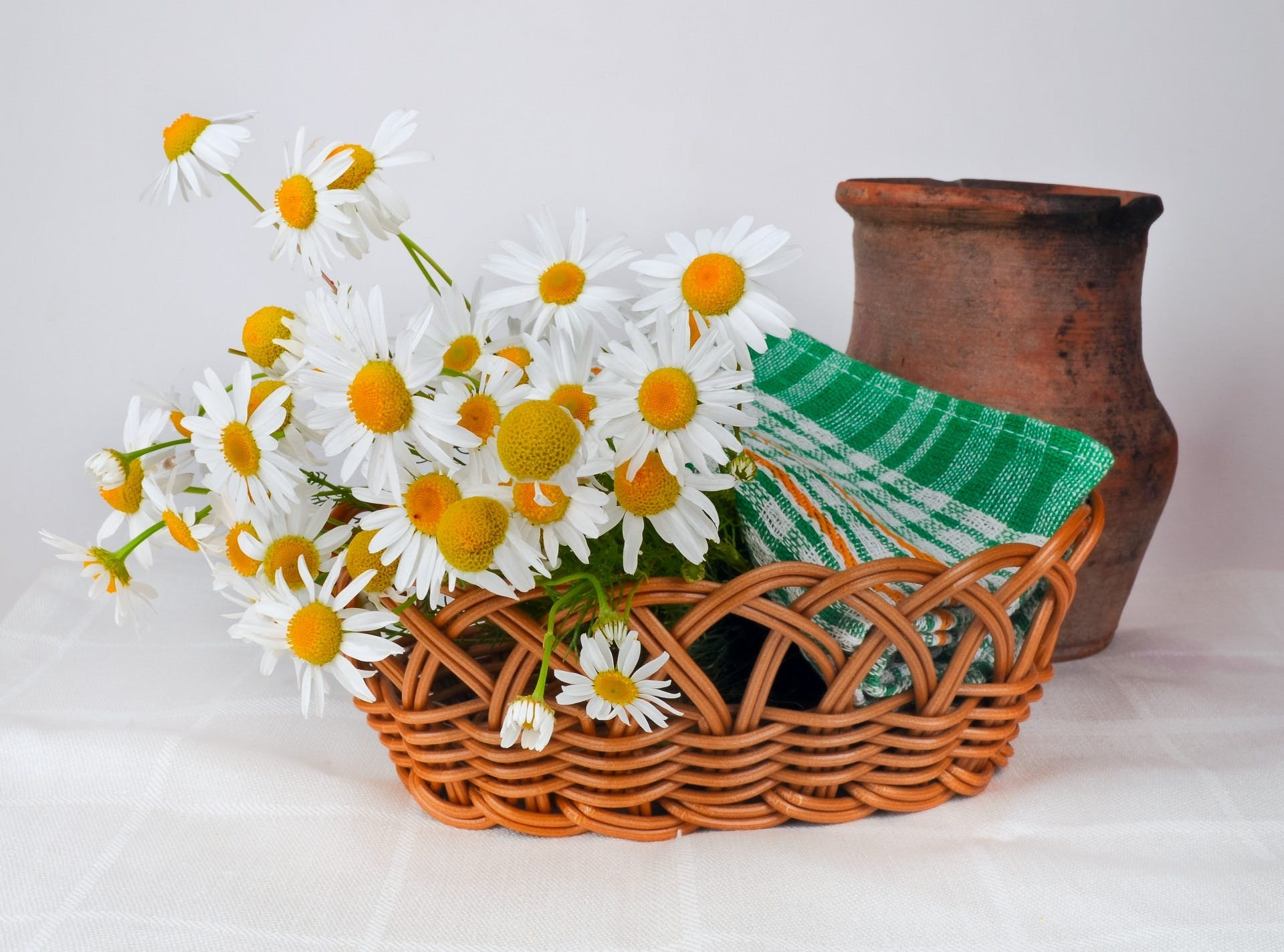 White and Orange Daisy Flowers on Brown Woven Basket Near Brown Vase