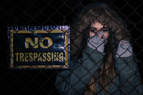Woman Behind Black Chainlink Fence With No Trespassing Signage