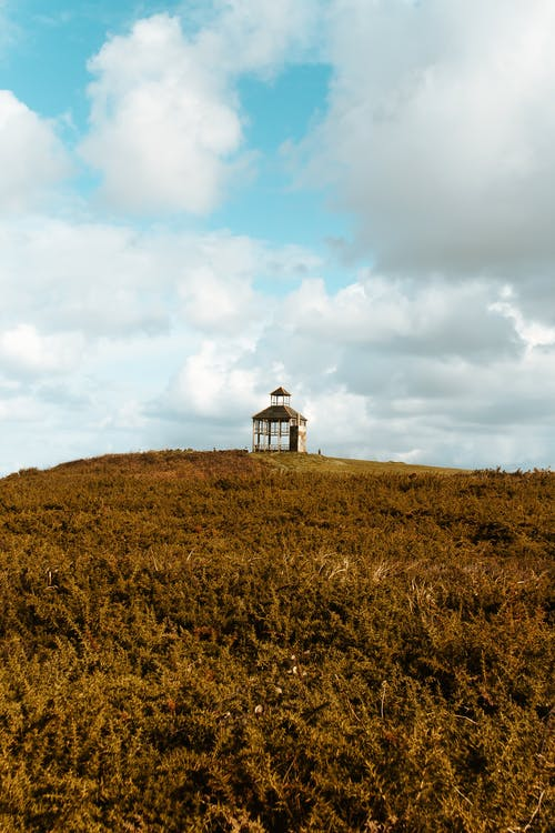 White and Black Lighthouse on Brown Grass Field Under White Clouds and Blue Sky