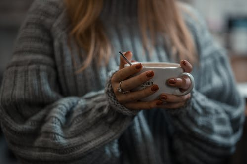 Woman in Gray Sweater Holding White Ceramic Mug