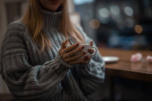 白いセラミックマグカップを保持している灰色のニットセーターの女性