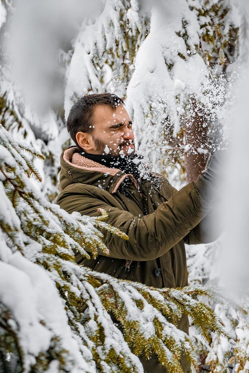 Man Standing Beside Tree With Snow