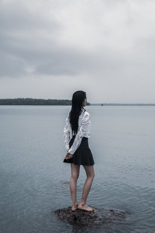 Woman Standing on Stone on Body of Water