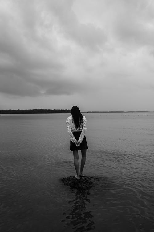 Woman Standing On A Rock In A Body Of Water