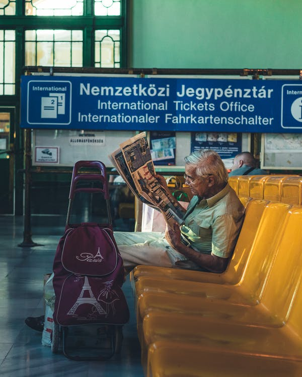 Man Sitting on Gang Chair While Reading a Book