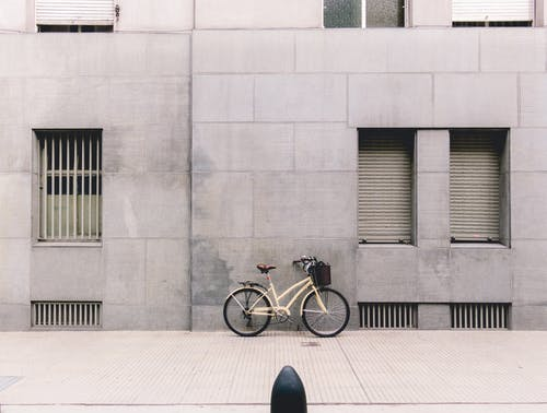 Bicycle parked against concrete building in