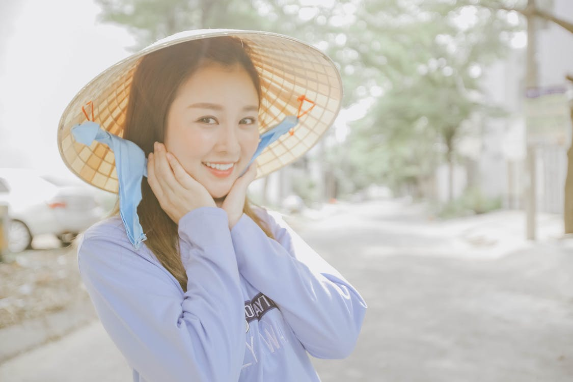 Smiling Woman Touching Her Face Wearing Hat