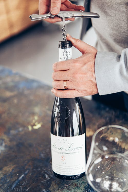 Photo Of Person Holding Wine Bottle