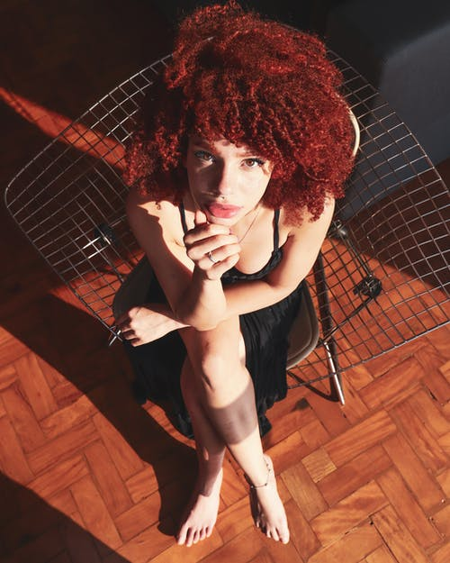Overhead Photo of Woman in Black Outfit Sitting on Chair Posing While Looking up