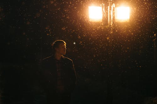 Man in Black Jacket Standing Near A Lamp Post