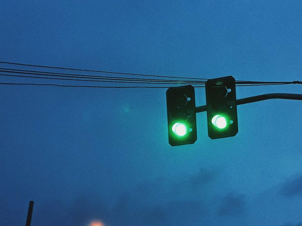 Green traffic light against dark sky