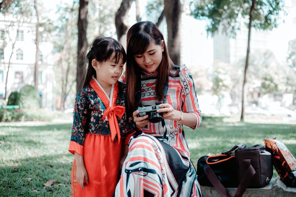 Girl Standing Beside Woman Using Camera