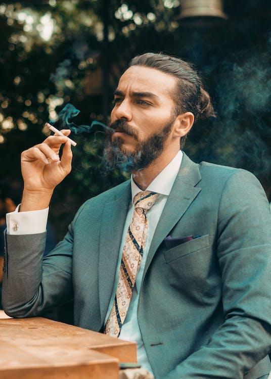 Man in Gray Suit Jacket Smoking Cigarette