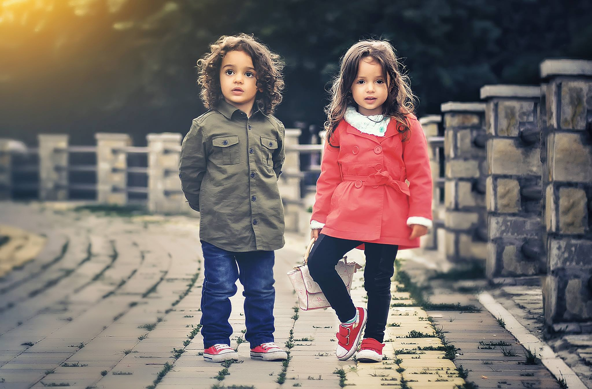 Two Children Standing Near Concrete Fence