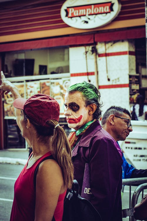 Man in Joker Costume Standing Beside Woman in Red Cap