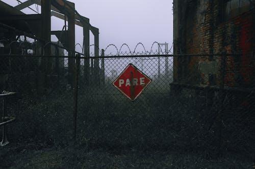 灰色金屬柵欄上的紅色和白色停止標誌