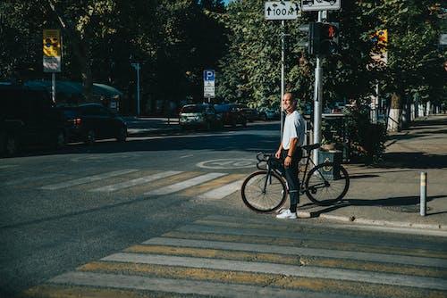 Man Holding Bike in Front of Pedestrian Lane