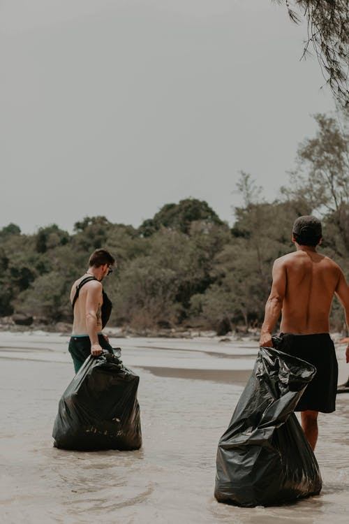 Shirtless men with trash bags on seashore