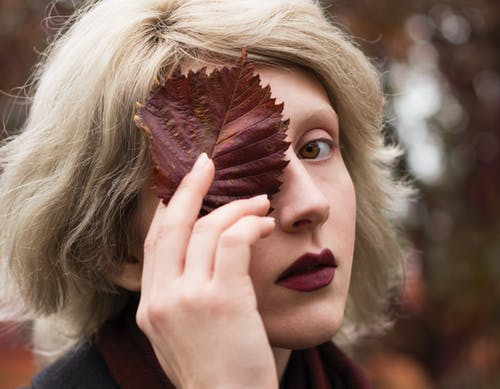 Shallow Focus Photography of Woman Covering Face With Leaf