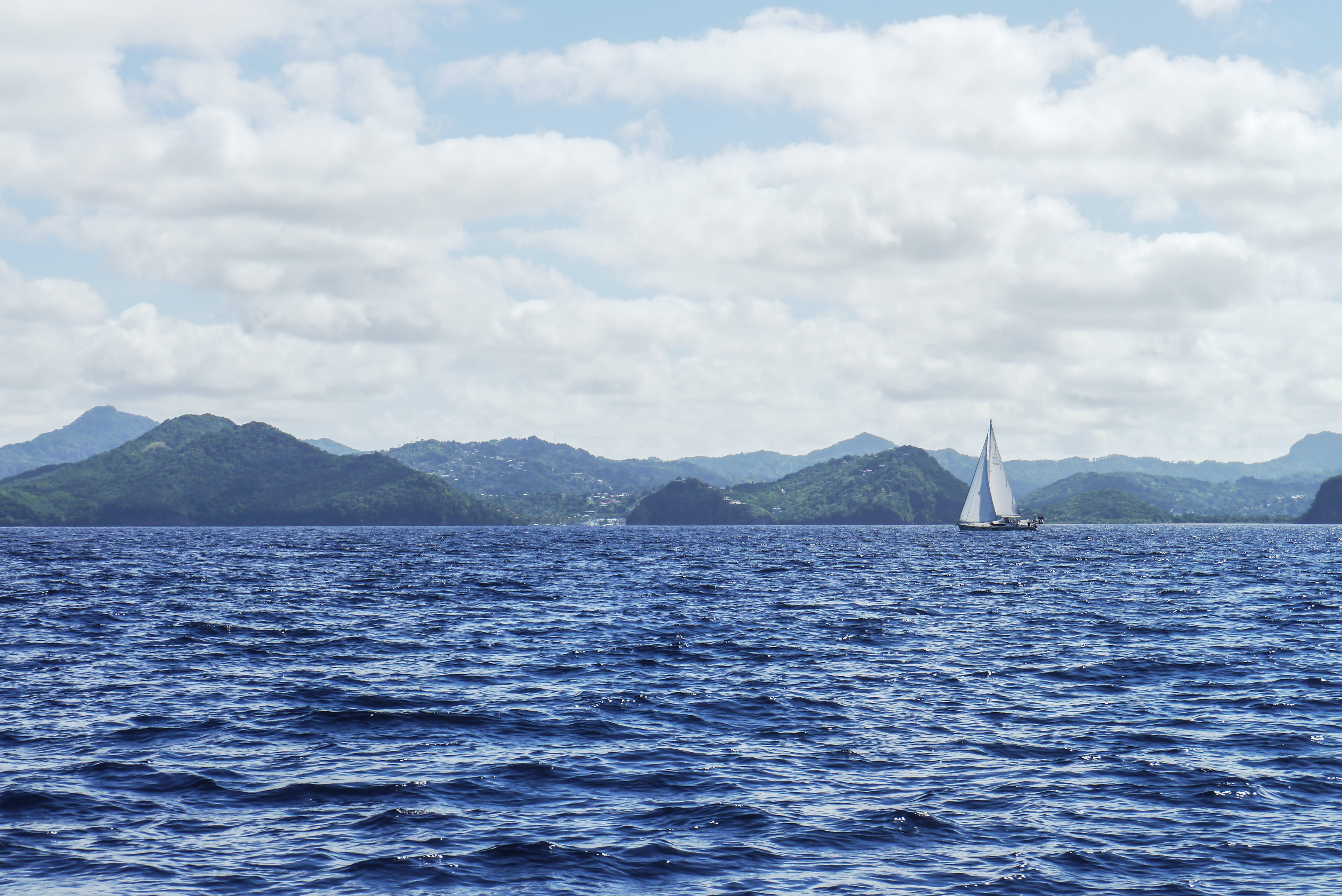White Boat With Sail on Body of Water