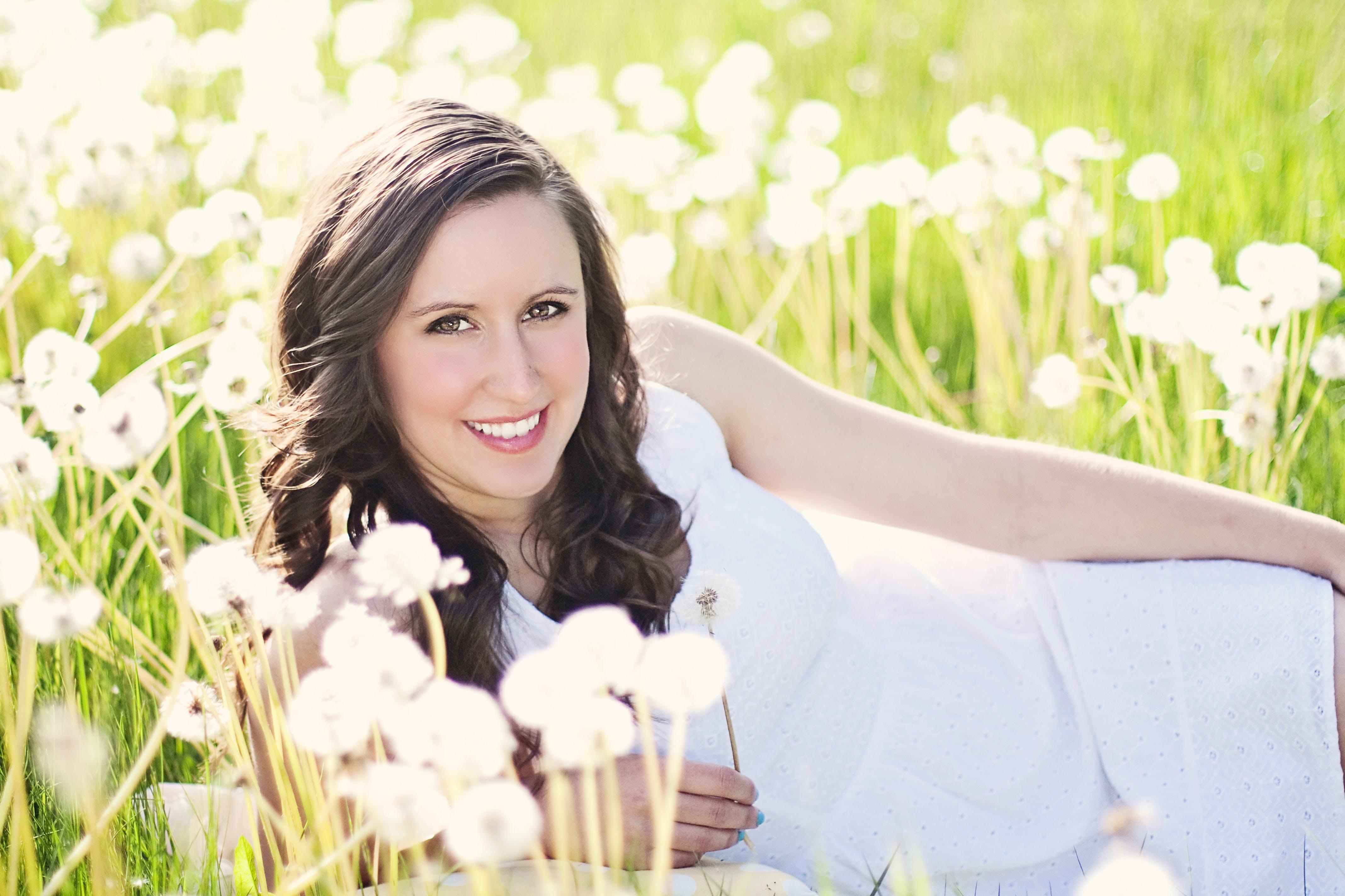 Woman in White Sleeveless Dress Lying on Green Grass Field