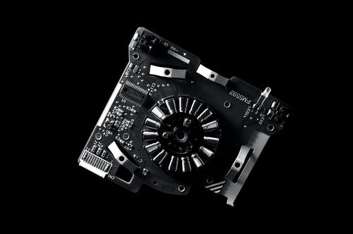 Greyscale Photo of Machine Part and Mother Board