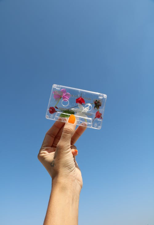 Person Holding White and Pink Floral cassette Tape