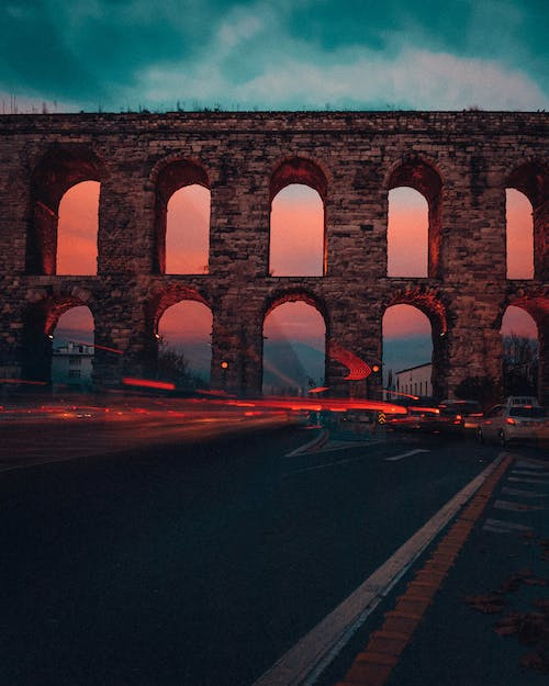 Traffic lights against aged aqueduct in sunset