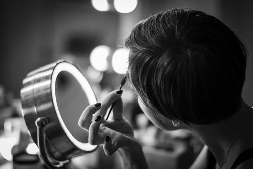 Grayscale Photo of Person Applying a Make-Up