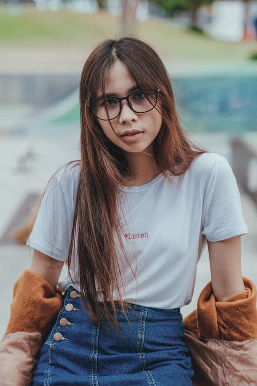 Shallow Focus Photography of Woman Wearing White Crew-neck Shirt and Blue Denim Skirt