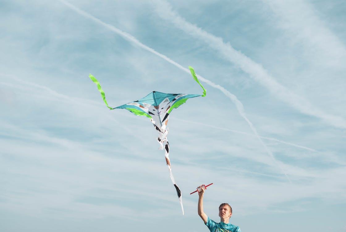 Man Wearing Blue Shirt Flying Kite