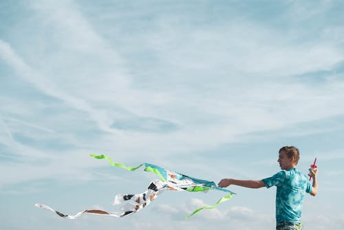 Teenager with waving kite against sky