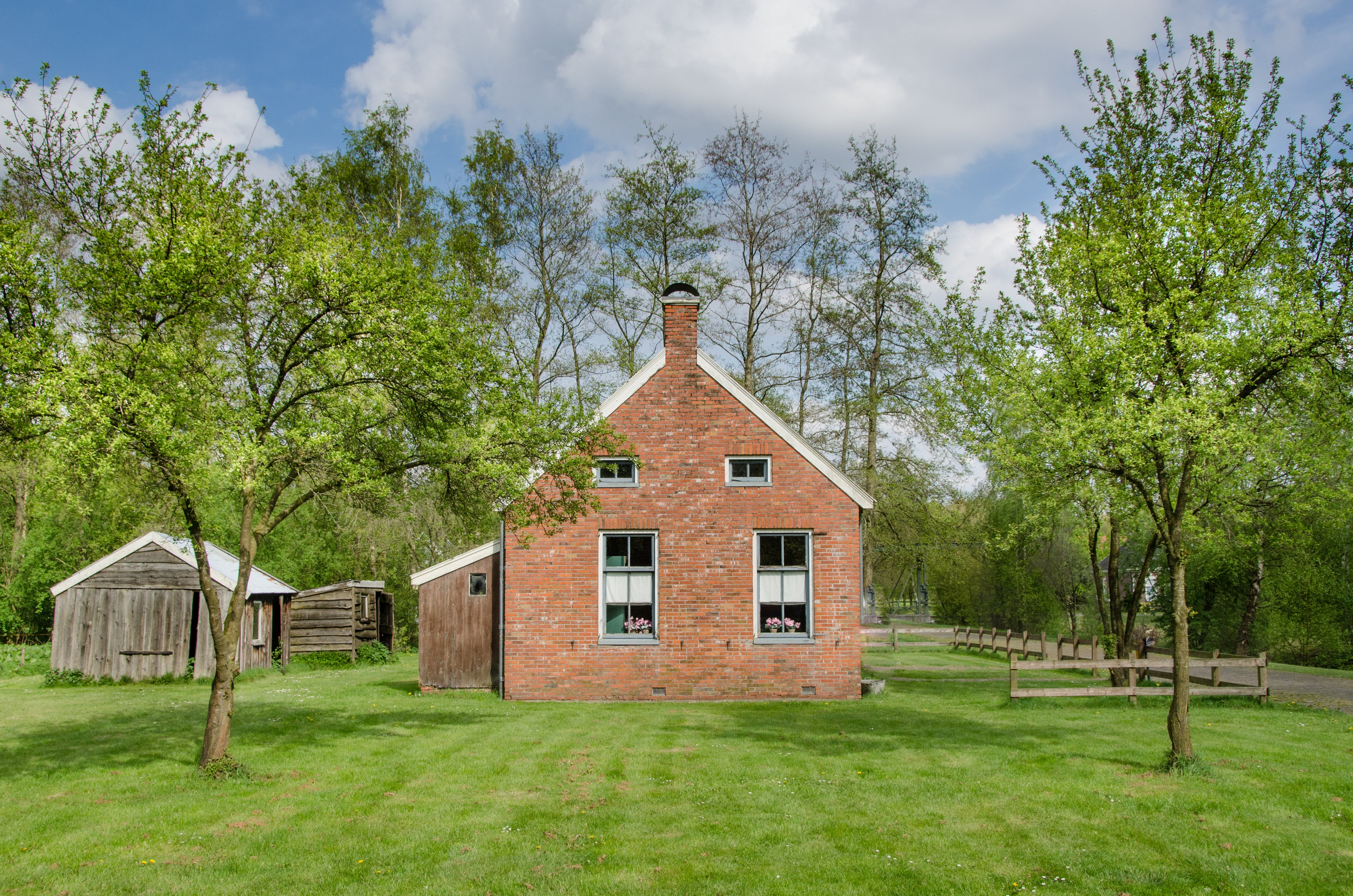 Brown Brick House Surrounded by Green Trees and Grass
