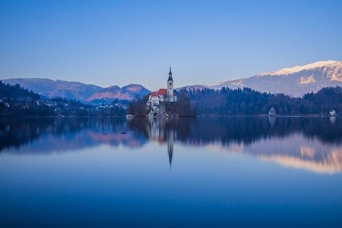 Body of Water Near Mountain Under Blue Sky