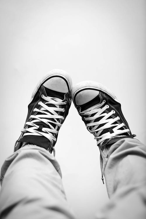 Grayscale Photography of Person Wearing Sneakers