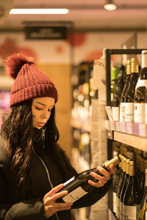 Woman picking wine in store