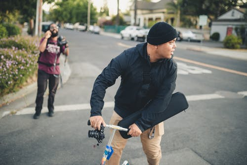 Man Standing on Scooter Holding a Camera