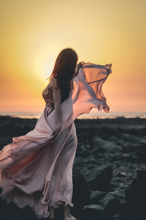 Back view of woman wearing silky maxi dress waving in wind standing sensually on rocky shore against sunset
