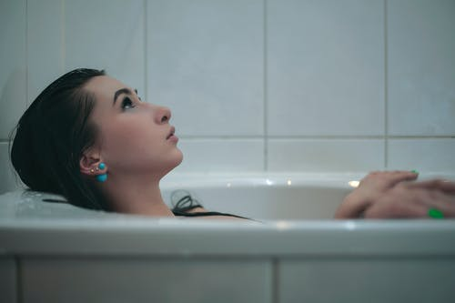 Woman Lying Down in Bathtub