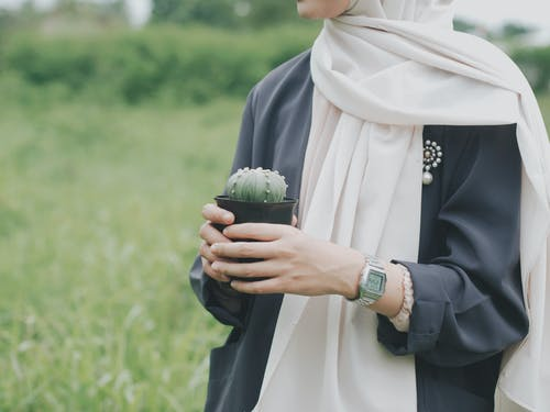 Woman Carrying Green Cactus Plant