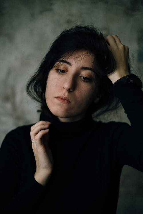 Woman Wearing Black Crew-neck Long-sleeved Shirt Standing While Touching Her Head