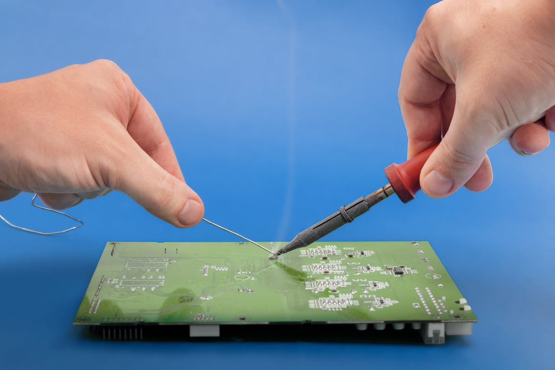 Person Holding Soldering Iron