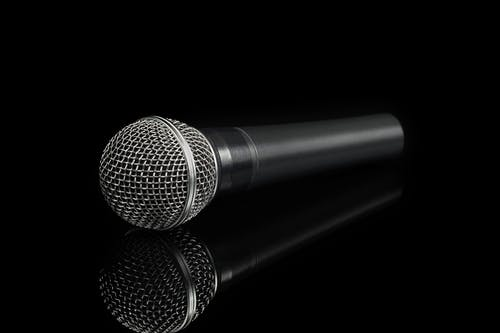 Black and Gray Dynamic Microphone on Reflective Surface