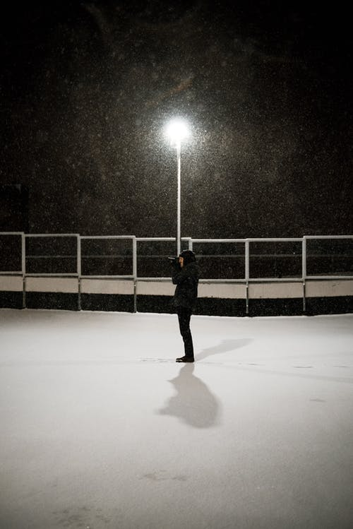 Man in Black Jacket Standing On White Snow